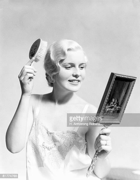 beautiful woman wearing slip, looking in mirror and brushing hair. - frau in slip stock-fotos und bilder