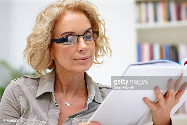 Beautiful woman wearing smart glasses reading a book