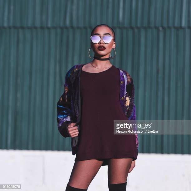 Beautiful Woman Wearing Sunglasses While Standing Against Corrugated Iron
