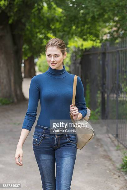 beautiful woman wearing turtleneck looking away while walking on sidewalk - col roulé photos et images de collection