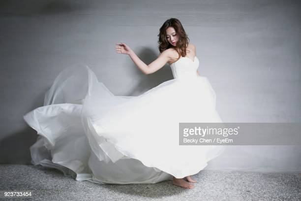 beautiful woman wearing wedding dress while standing against wall - ドレス ストックフォトと画像