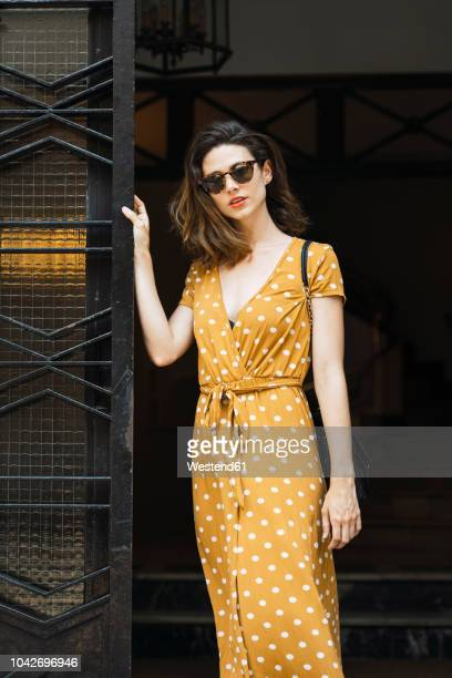 beautiful woman wearing yellow dress with polka dots - kleid stock-fotos und bilder