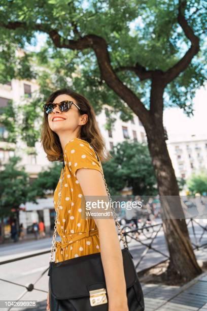 beautiful woman wearing yellow dress with polka dots, walking in the city - gelbes kleid stock-fotos und bilder