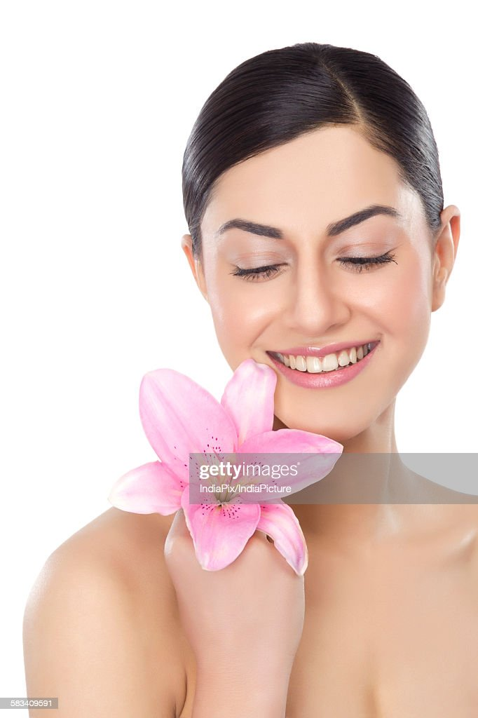Beautiful woman with a flower smiling : Stock Photo
