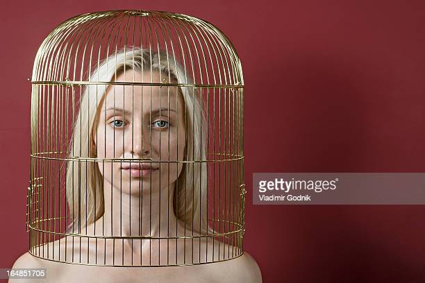 A beautiful woman with a gold birdcage over her head