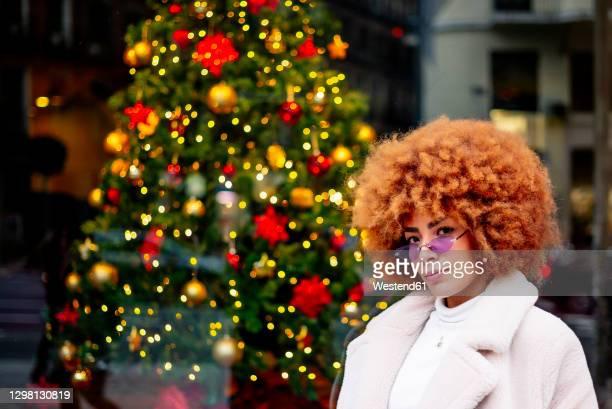 beautiful woman with afro hair standing against illuminated christmas tree in city - kroeshaar stockfoto's en -beelden