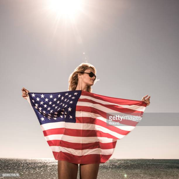 Beautiful woman with American flag in summer day.