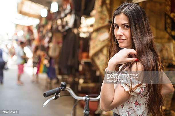Bella mujer con bicicleta en florence mercado local