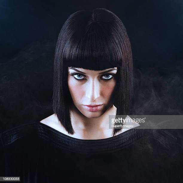 beautiful woman with blunt dark hair and smoky black background - beautiful dominant women stock pictures, royalty-free photos & images