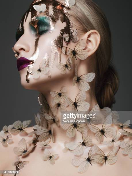 Beautiful woman with butterflies and liquid gold on her face