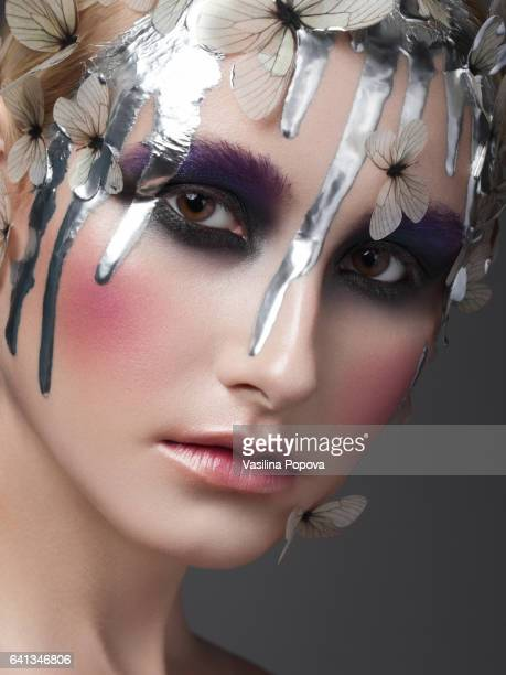 Beautiful woman with butterflies and liquid silver on her face