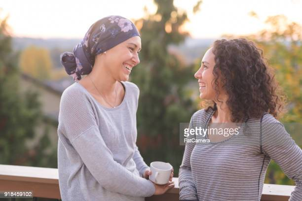 beautiful ethnic woman with cancer talks with her sister - cancer illness stock photos and pictures