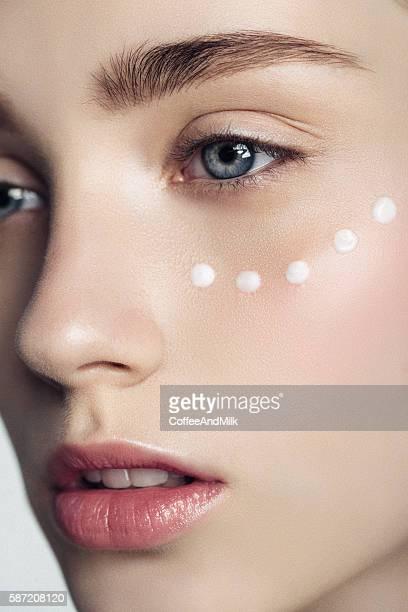 beautiful woman with cream dots on the face - kosmetische behandlung stock-fotos und bilder