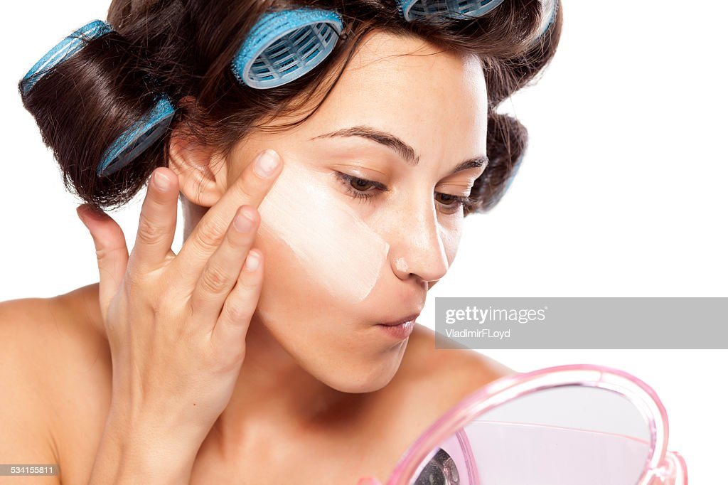 Beautiful woman with curlers applying poorly chosen foundation : Stock Photo
