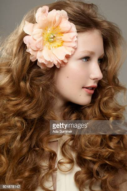 beautiful woman with curly dark blonde hair and a peony in her hair