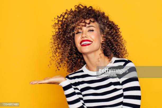 beautiful woman with curly hair demonstrates your product - pop musician stock pictures, royalty-free photos & images