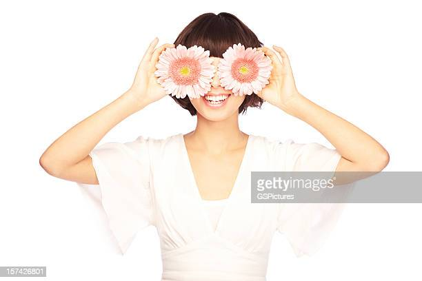 Beautiful woman with daisies in front of her eyes