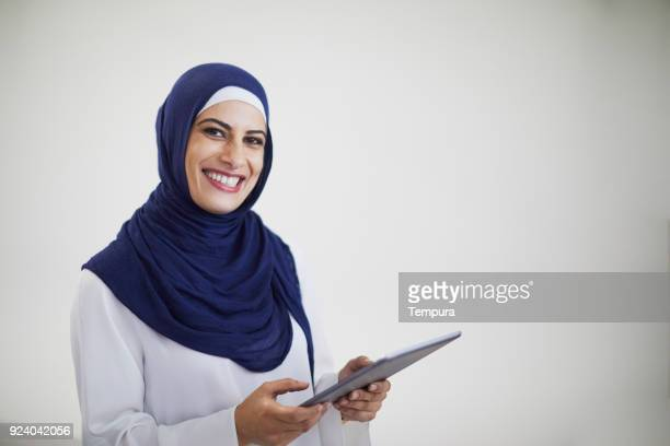 Beautiful woman with digital tablet on grey background.