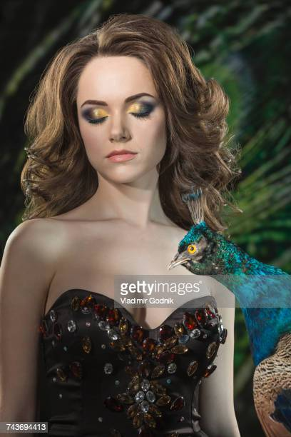 Beautiful woman with eyes closed by peacock against feathers