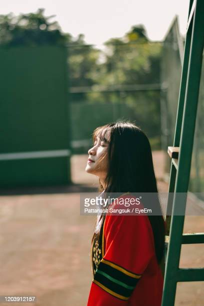 beautiful woman with eyes closed standing by ladder - pattanasit stock pictures, royalty-free photos & images