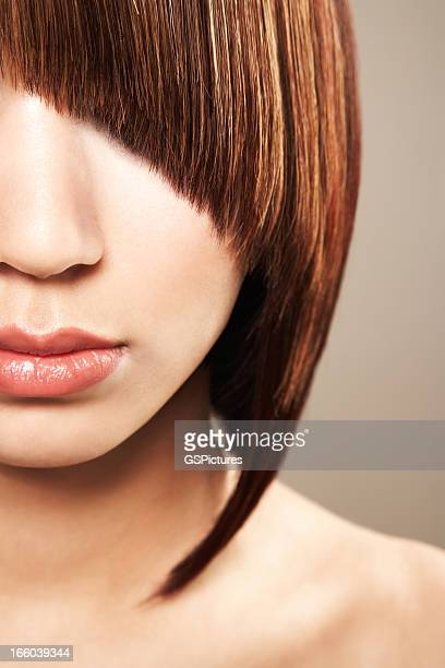 Beautiful woman with eyes obscured by dramatic curved bangs