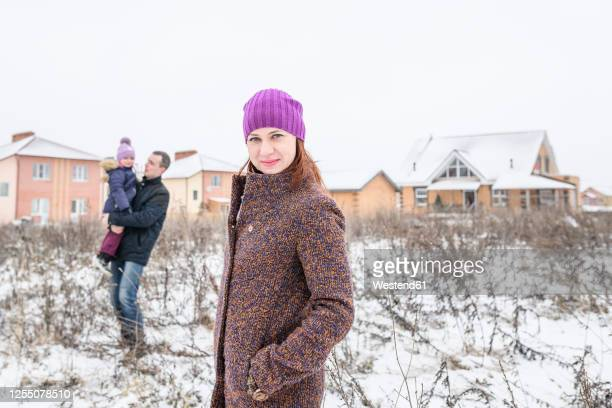 beautiful woman with father and daughter in background during winter - mains dans les poches photos et images de collection