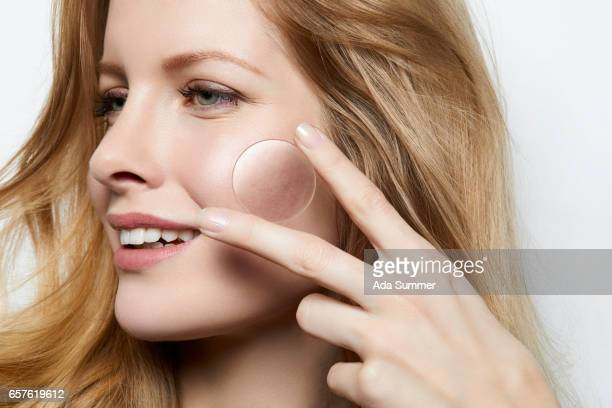 beautiful woman with flawless skin holding a magnifying glass over a part of skin with acne