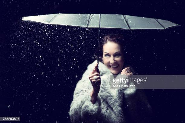 Beautiful woman with fur coat standing in rain under an umbrella at night - Studio, South Africa