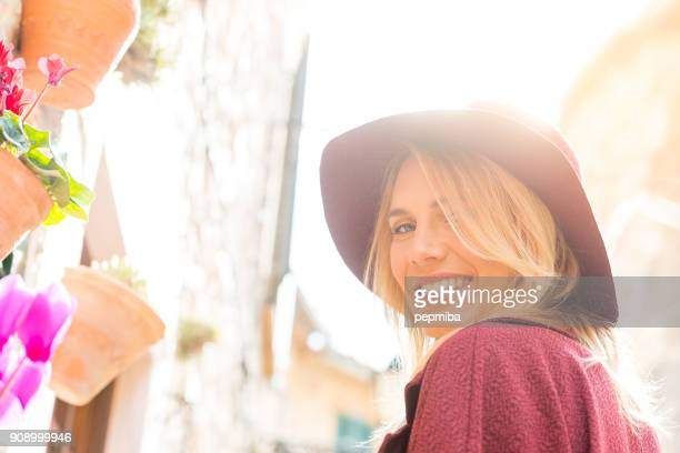 beautiful woman with garnet coat and hat - mid adult stock pictures, royalty-free photos & images
