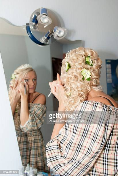 Beautiful Woman With Hairstyle Applying Make-Up Reflecting In Mirror At Home