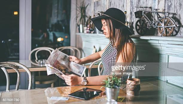 Schöne Frau mit Hut Lesen der Zeitung