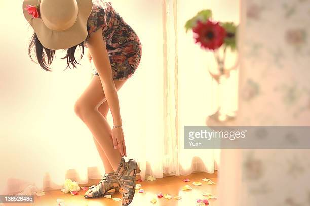 beautiful woman with hat touching her sandals - サンダル ストックフォトと画像