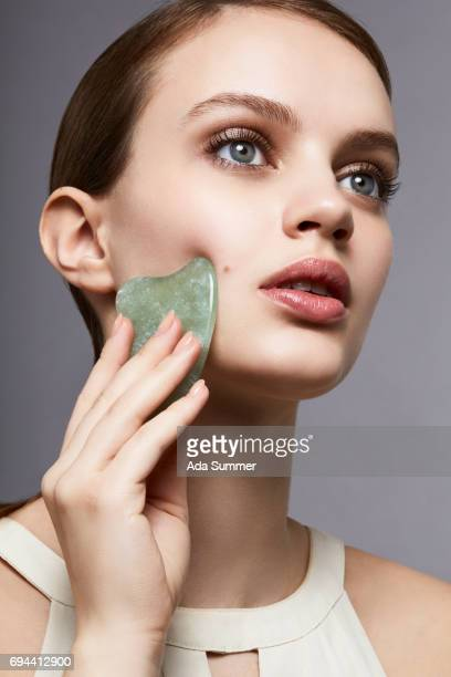 beautiful woman with jade massaging stone on her cheek