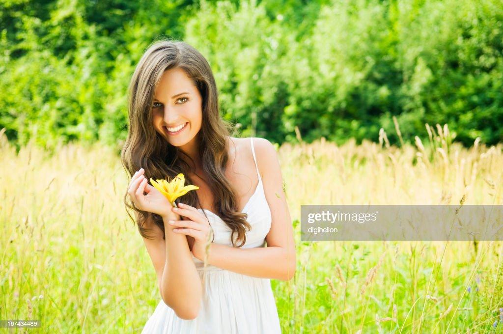 lilly hermosa mujer con flor en el prado con : Foto de stock
