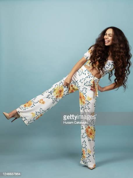 hermosa mujer con el pelo largo rizado en traje floral frente de fondo azul - moda fotografías e imágenes de stock