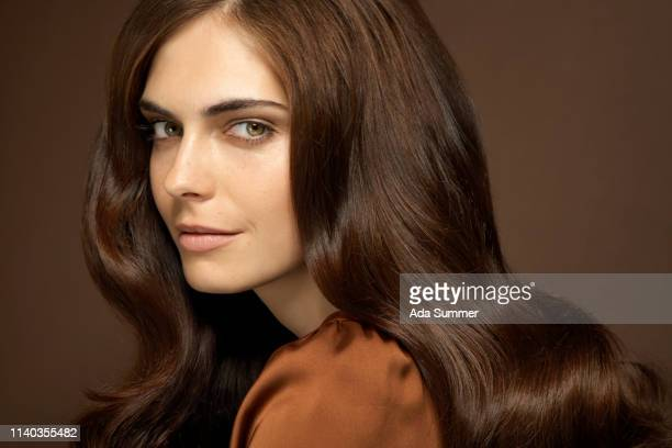 beautiful woman with long dark blond wavy hair - brown hair stock pictures, royalty-free photos & images