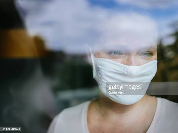 beautiful woman with mask looking out window. - abstand halten infektionsvermeidung stock-fotos und bilder