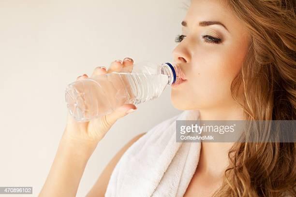 Schöne Frau mit Flasche Wasser und Handtuch
