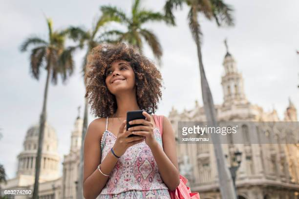 Beautiful woman with mobile phone standing in city