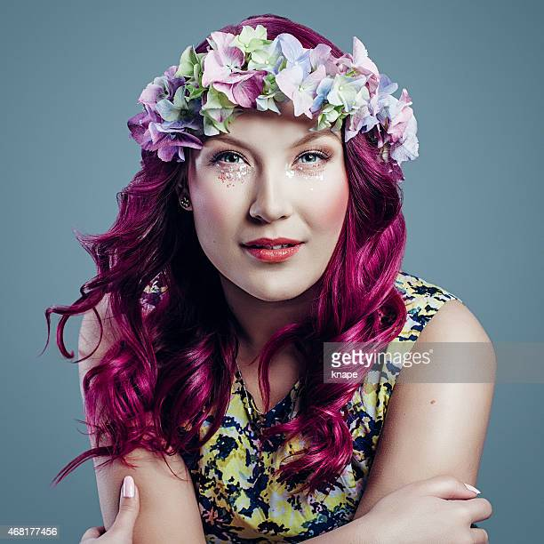 Beautiful woman with pink hair and flower garland