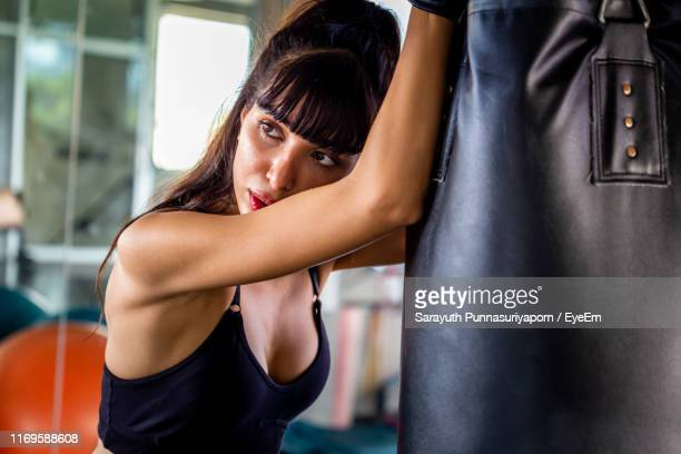 beautiful woman with punching bag in gym - punching stock pictures, royalty-free photos & images