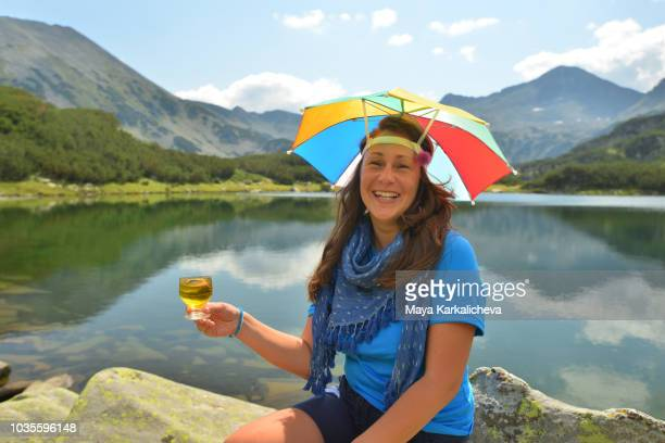 beautiful woman with rainbow hat smiling by a mountain lake - pirin mountains stock pictures, royalty-free photos & images
