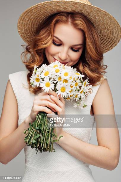 beautiful woman with red hair holding bouquet - chamomile tea stock photos and pictures