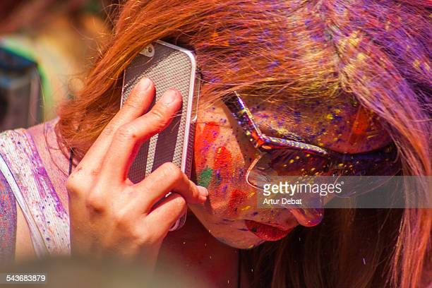 Beautiful woman with red lips talking with his smartphone on ear covered with colorful Gulal powder on the Holi festival of Barcelona Catalonia Europe