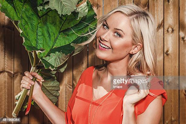 Beautiful woman with rhubarb outdoors in summer