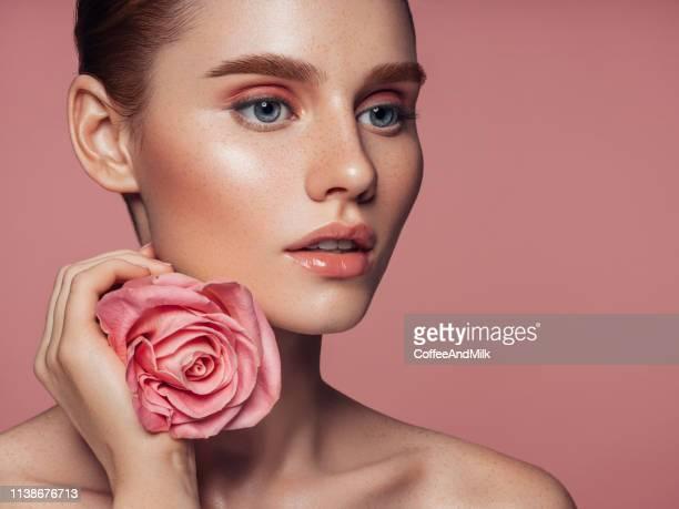 beautiful woman with rose. natural soft make-up. - occhi azzurri foto e immagini stock