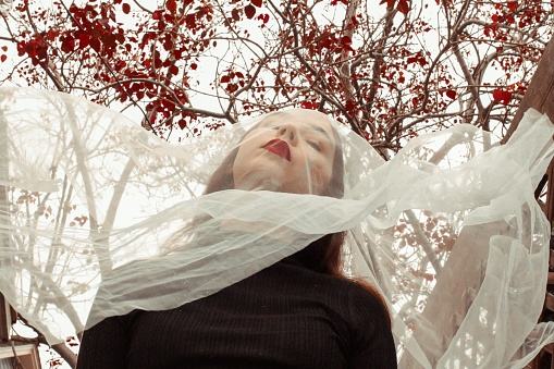 Beautiful Woman With Scarf Against Tree - gettyimageskorea