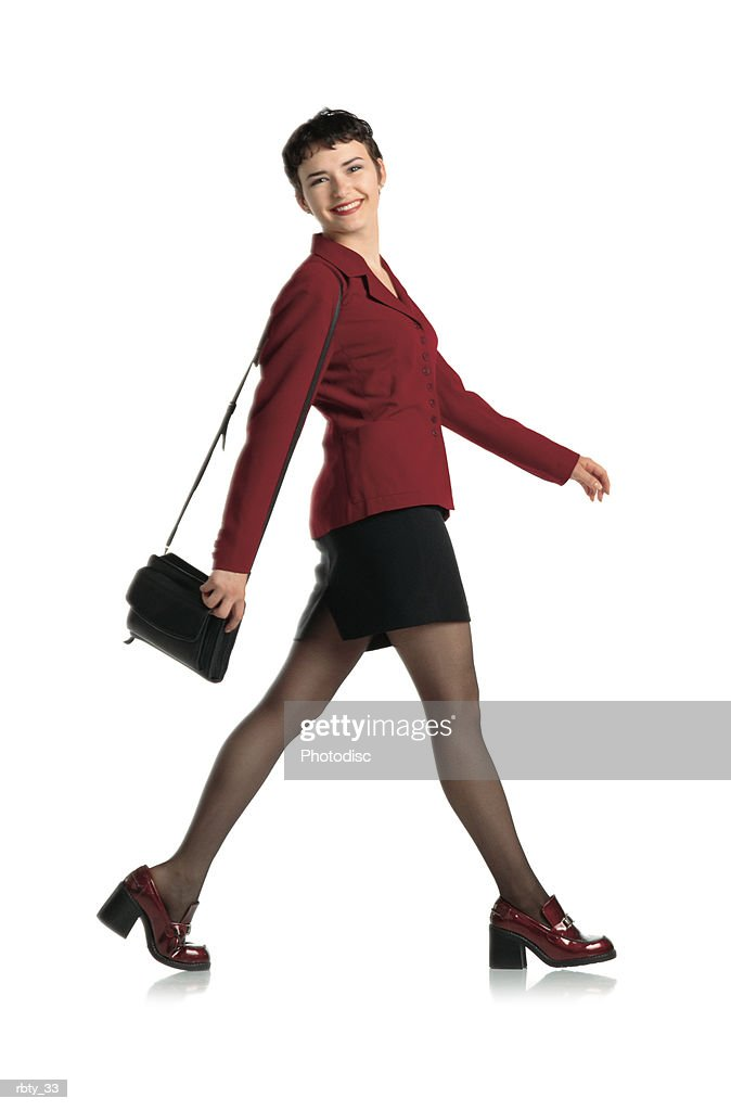 beautiful woman with short dark hair wearing a black mini skirt maroon blazer black nylons red high heeled shoes and purse struts in front of the camera holding her purse and smiling : Stockfoto