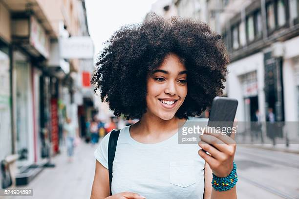 Beautiful woman with smart phone walking on the street