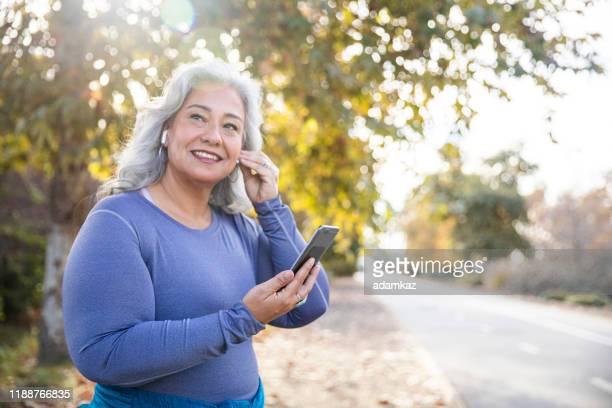 schöne frau mit smartphone immer bereit für das training - mollige frau stock-fotos und bilder